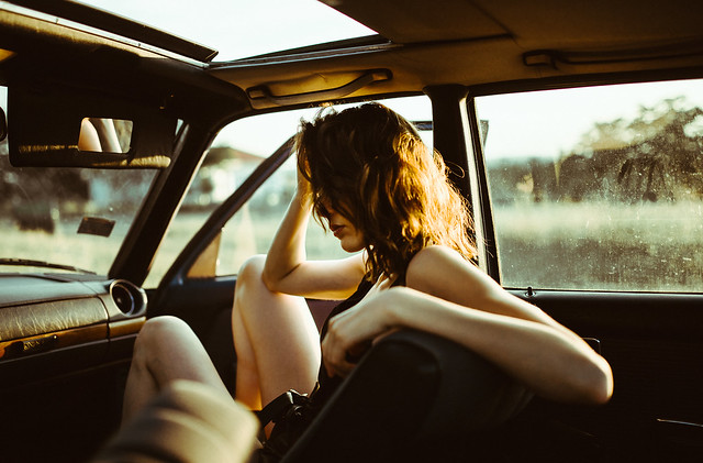 Portrait of a woman sitting in a car during golden sunset.