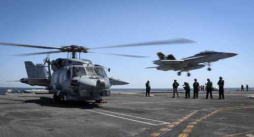 An SH-60R Sea Hawk helicopter turns as an F/A-18F Super Hornet prepares to land aboard USS Abraham Lincoln (CVN 72).