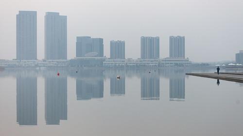yixing wuxi jiangsu china prc sunrise dawn softlight water reflections calm mirror dongjiu lake highrise skyscrapers buildings city architecture tall