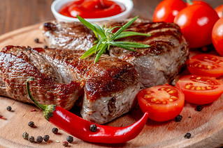 Delicious steaks with rosemary, tomatoes, chili and sauce on wooden kitchen Board | by wuestenigel
