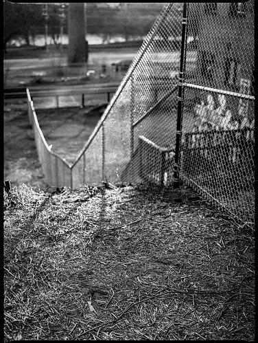 embankment lookingdown chainlinkfence riverdistrict nearsunset backlit asheville northcarolina frenchbroadriver railroadtracks mamiya645pro mamiyasekor80mmf28 mamiyaprime primelens monochrome monochromatic blackandwhite 120 120film film mediumformat 645