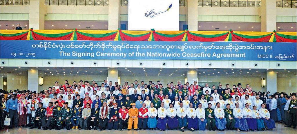 ตัวแทนกองกำลังกลุ่มชาติพันธุ์ 8 กลุ่ม และตัวแทนรัฐบาลพม่านำโดยประธานาธิบดีเต็ง เส่ง ถ่ายภาพร่วมกันเป็นที่ระลึก หลังพิธีลงนามข้อตกลงหยุดยิงทั่วประเทศ (NCA) ที่เนปิดอว์ เมื่อ 15 ตุลาคม 2015 และในเดือนกุมภาพันธ์ปี 2018 มีอีก 2 กลุ่มเข้าร่วม รวมเป็น 10 กลุ่ม (ที่มา: แฟ้มภาพ/The Global New Light of Myanmar, 16 October 2015)