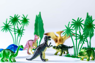Toy dinosaurs and trees on white background | by wuestenigel