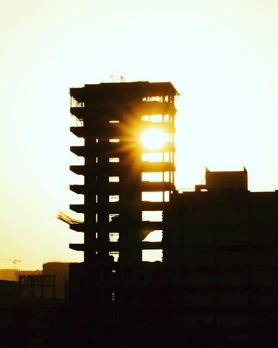 evening timing tower suburban town city apartment building underconstruction peepingsun rays sunrays sunlight sunset sun
