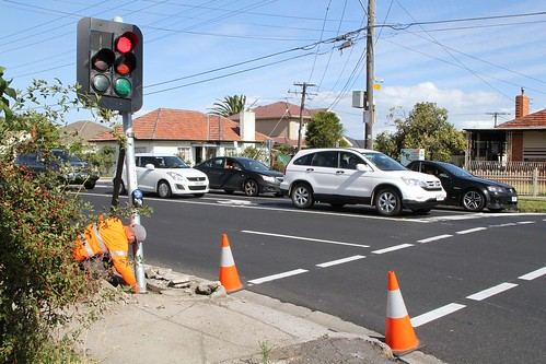 VicRoads contractors use a jack to try and bend the traffic signal post back into place