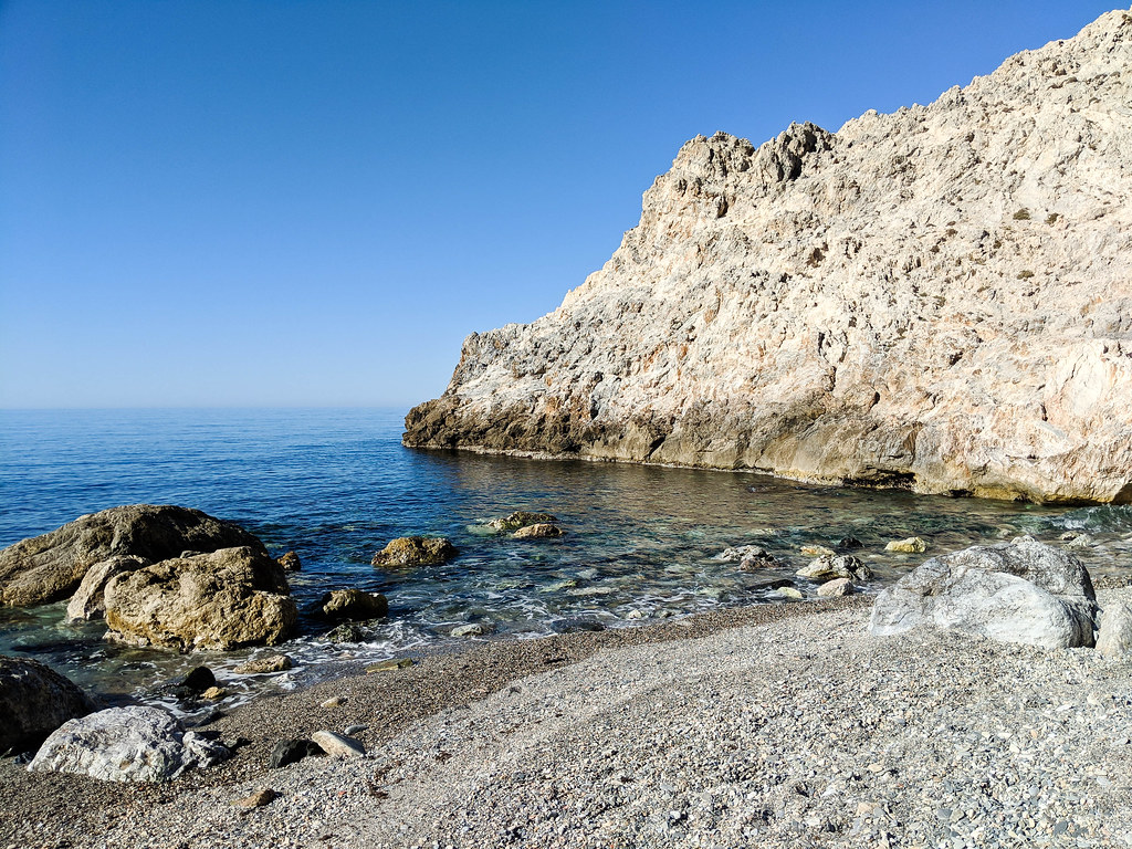 A rocky beach next to a cliff emerging from the sea