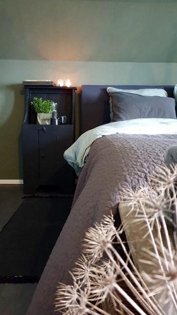 Donkerblauw nachtkastje groene muur slaapkamer