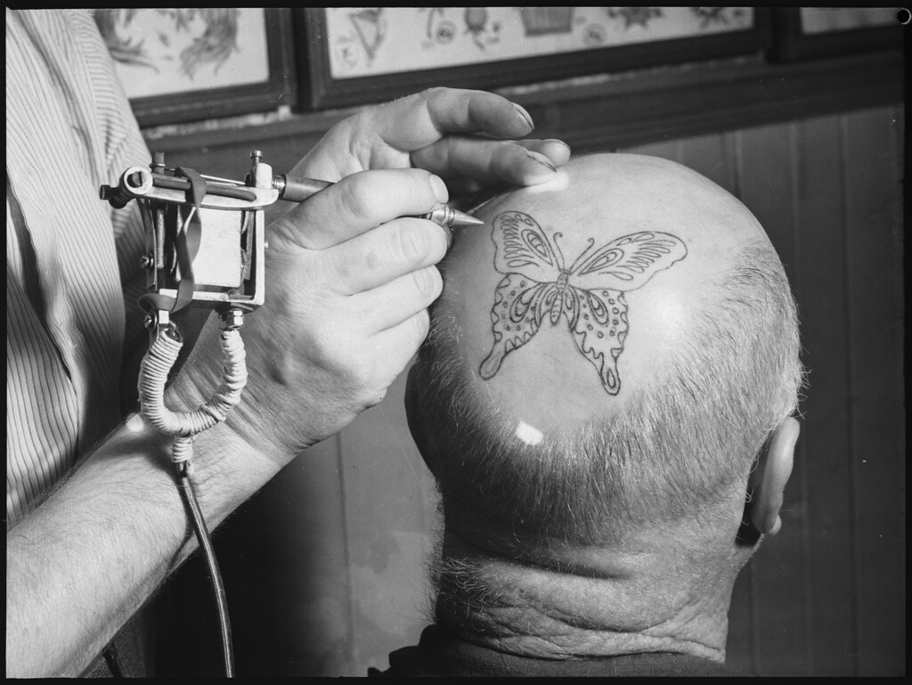 Tattooing a mans head with a butterfly, Fred Harris Tattoo