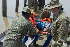 Malaysian first responders and Royal Air Force Reserves Flight Lieutenant John Carolan-Cullion lift a civilian with simulated injuries from a boat during a field training exercise as part of Pacific Partnership 2019. (U.S. Navy/MC2 William Berksteiner)
