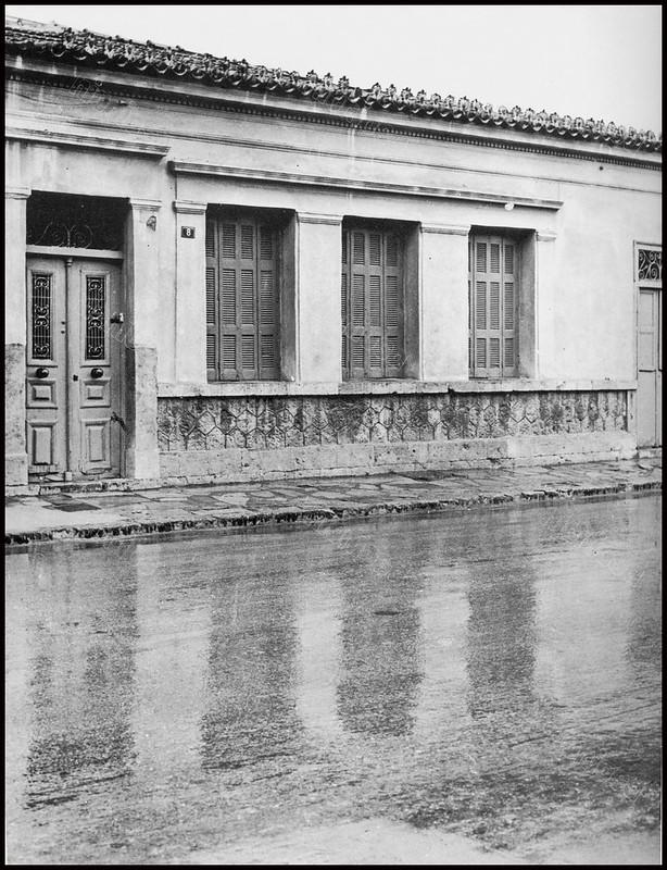 """Στον Πειραιά μετά από βροχή. Φωτογραφία του Στέλιου Σκοπελίτη από το βιβλίο """"Νεοκλασσικά σπίτια της Αθήνας και του Πειραιά"""" Εκδόσεις """"Δωδώνη"""", Αθήνα, 1975."""