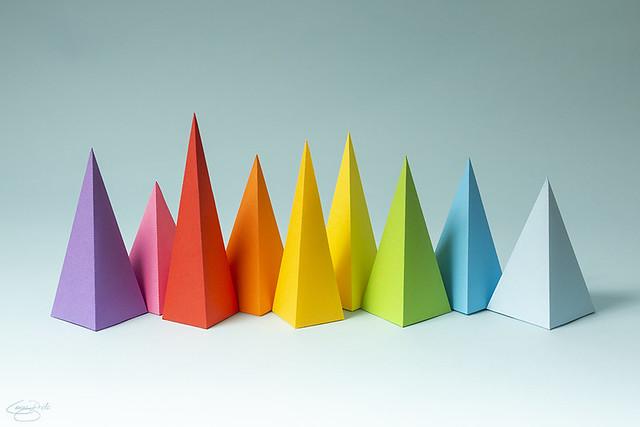 Rainbow pyramid shapes arranged on a bright blue background. (1)