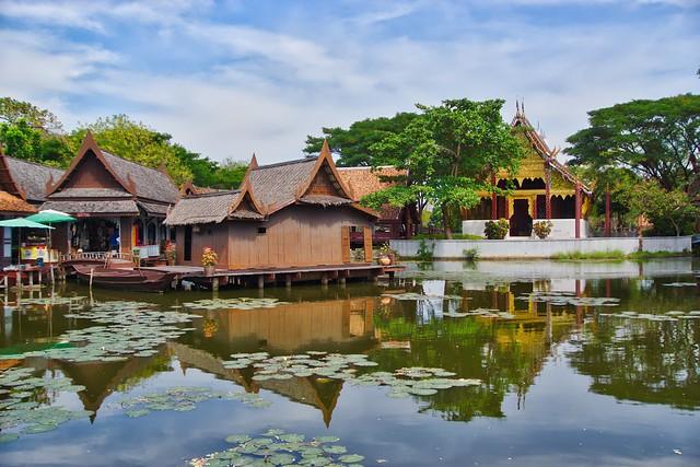 Lake with replica of traditional Thai village in Muang Boran open air museum in Samut Phrakan, Thailand