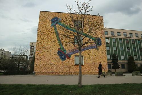 moving car motion photography buildings sky tree graffiti lady woman walking sidewalk street view grass people daily life travel explore sarajevo bosnia balkans