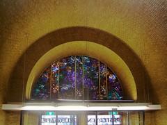 <p>Gebrandschilderd raam boven de ingang. Foto: Geerten van Gelder.</p>