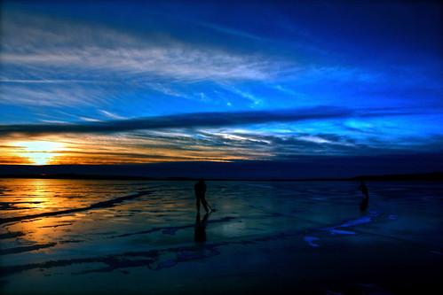 blue light sunset sun lake ice hockey minnesota yellow clouds frozen north skate stick silouhette