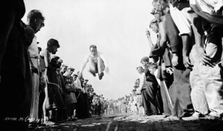 Man doing a long jump as part of a track and field event, August 1933 / Homme faisant un saut en longueur dans le cadre d'exercices d'athlétisme, août 1933