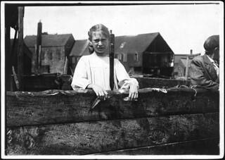 Minnie Thomas, 9 years old, showing the average size of the sardine knife as large as this. Eastport, Me, August 1911