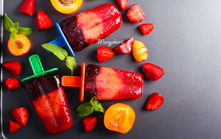 Berry and fruit ice cream pops on black surface | by manyakotic