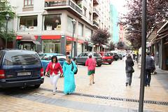 Vehículos estacionados a las izquierda y personas por el centro