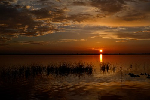 sunset sky sun lake water clouds