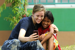 A Sailor takes a photo with a Thai girl during a community service event at The Child Development and Protection Center in Huay Yai, Thailand. | by Official U.S. Navy Imagery