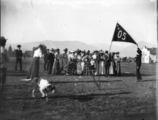 Members of the Pomona College class of 1905 wave a large class pennant on the field beside Renwick Gymnasium