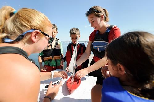 Using a miniature replica, undergraduate student instructors Katlyn Putney, left, and Ella Stutz, center, teach sailboat maneuvers.