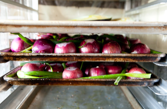 Sheet pans of fresh red onions and scallions