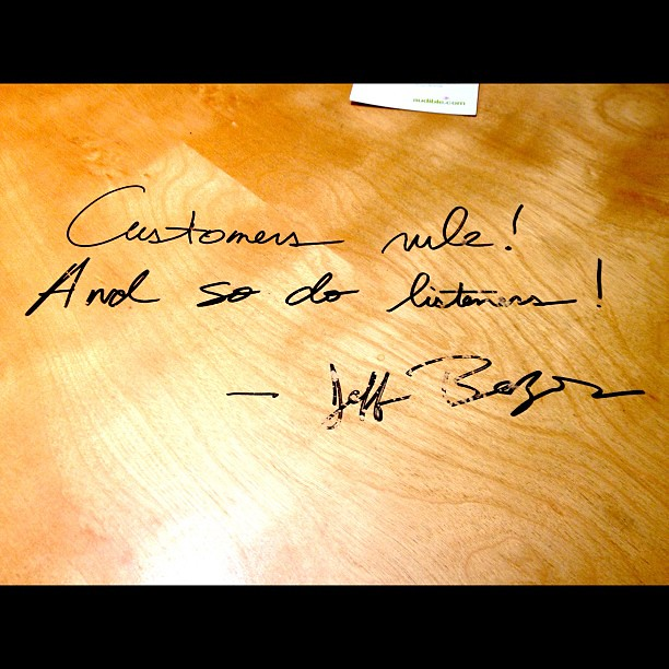 """Pic: """"Customers rule! And so do listeners! - Jeff Bezos"""" Autographed in a door-table of Audible, an Amazon co."""