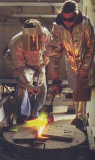 Michael Parker '00 (in face shield) and Matt Furmanski, lecturer in art, preparing molten bronze in the sculpture studio