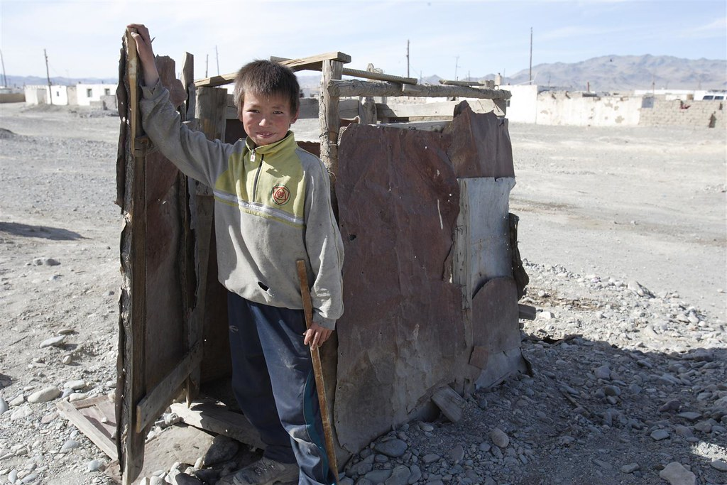 Child poverty in Mongolia | A boy walks out of a ramshackle