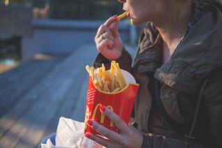 Girl eating french fries   by freestocks.org