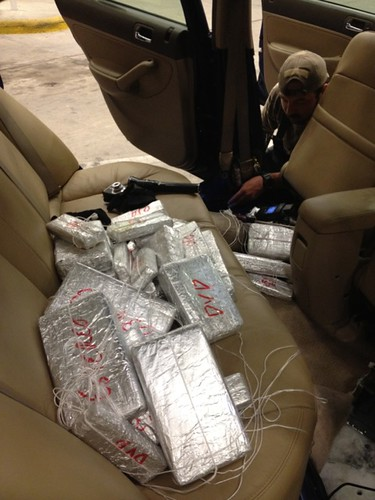 <p>CBP agents dig deep into this sedan to find packages of illegal drugs that are curiously labelled.</p>