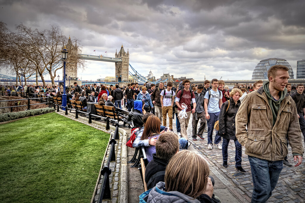 People walking along south bank of the Thames near Tower B