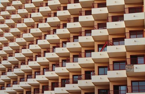 imagen de balcones iguales sin diferenciación en un edificio enorme a excepción de uno. Metáfora de ventaja competitiva