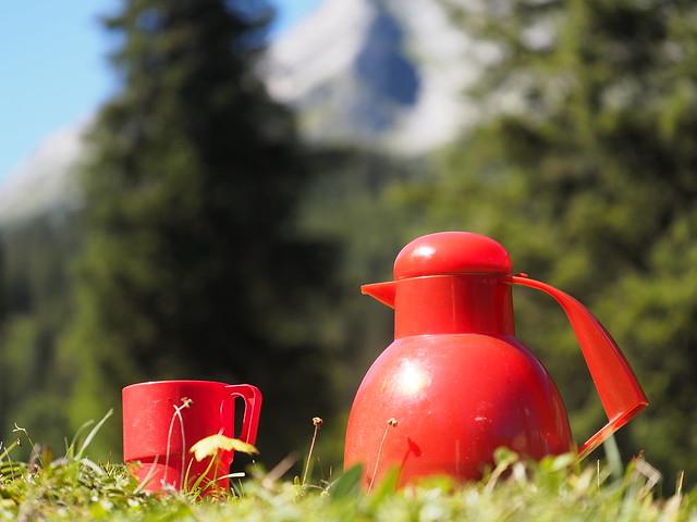 Rote Thermoskanne draußen in den Bergen - Red Thermos Bottle Outdoor Mountainside