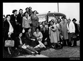 Group of young women standing hear a bus, apparently before migrating to Australia