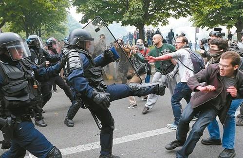 圖12.法國鎮暴警察與反對勞動法規改革的示威者在巴黎街頭正面衝突,五月廿六日一名員警甚至出腿踹人。 美聯社