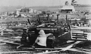 Two children sitting with a badly damaged piano amongst the debris from the Port Douglas cyclone of 1911