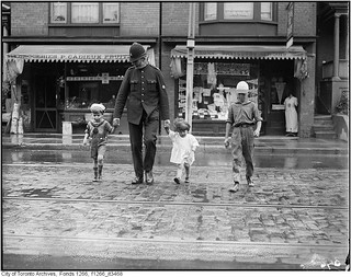 Policeman escorting children across Gerrard Street East