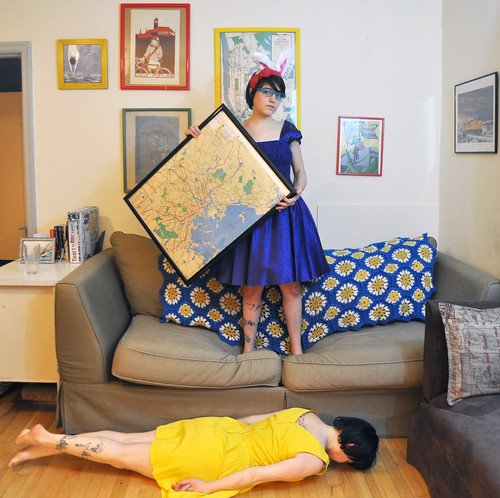 Day 47: Portrait of a Woman Laying Facedown in Front of a Sofa While Another Woman in Bunny Ears Holds a Boston T Map Circa 1980