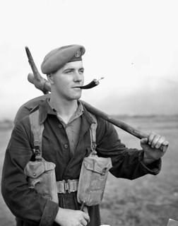 Unidentified man smoking a cigarette and holding a pickaxe / Homme non identifié fumant une cigarette, une pioche hache à la main