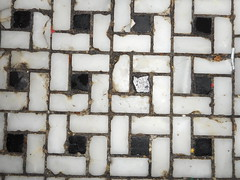 black and white tile floor with accumulated food in the grout between tiles