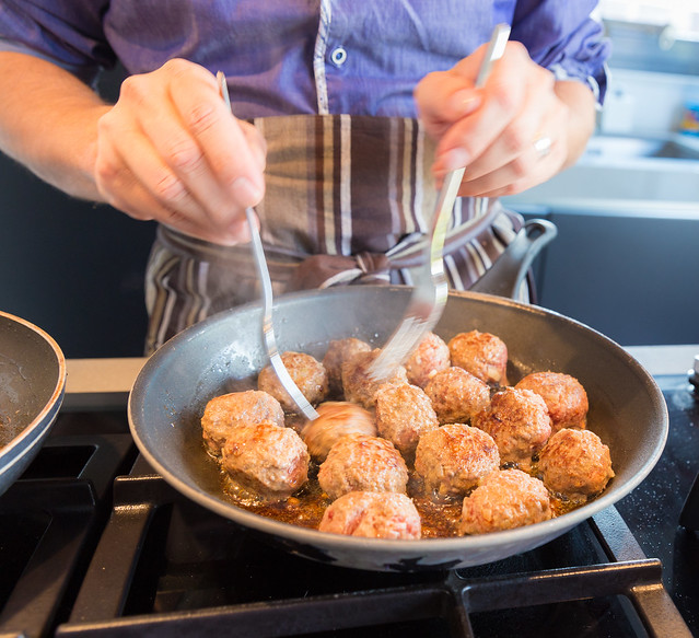 Chef turning meatballs in the frying pan