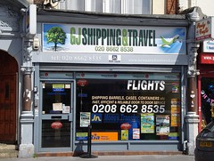 "The same shopfront, looking very similar to the previous photo.  The only obvious changes are a new sign reading ""GJ Shipping & Travel"", the removal of the words ""Cheap"" and ""Worldwide"" from the offer of ""Cheap Flights Worldwide"", and a slightly different selection of window decals."