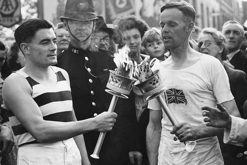 Veteran runner H J Bignall (right) hands over the Olympic torch to Fred Prevett at Redhill, Surrey, during the flame's journey from Dover to Wembley Stadium, London, for the opening of the 1948 London Olympics ©ROH/2012 | by Royal Opera House Covent Garden