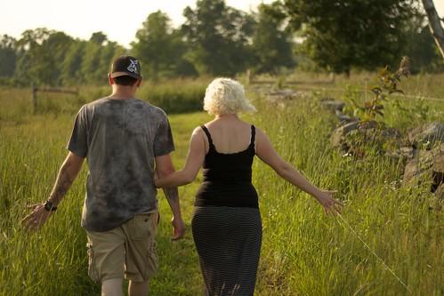 sunset green grass walking couple
