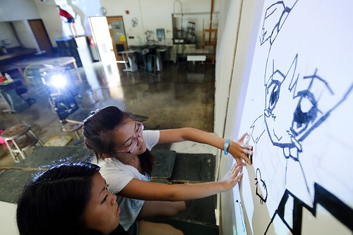 High school students Yer Lee, wearing glasses, and Mia Yang create a tape mural.