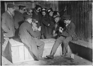 Flashlight photo of messengers absorbed in their usual game of poker in the Den of the terrible nine, March 1909