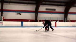 Brad Perry teaching a hockey player to skate with the puck at a hockey clinic | by Brad Perry
